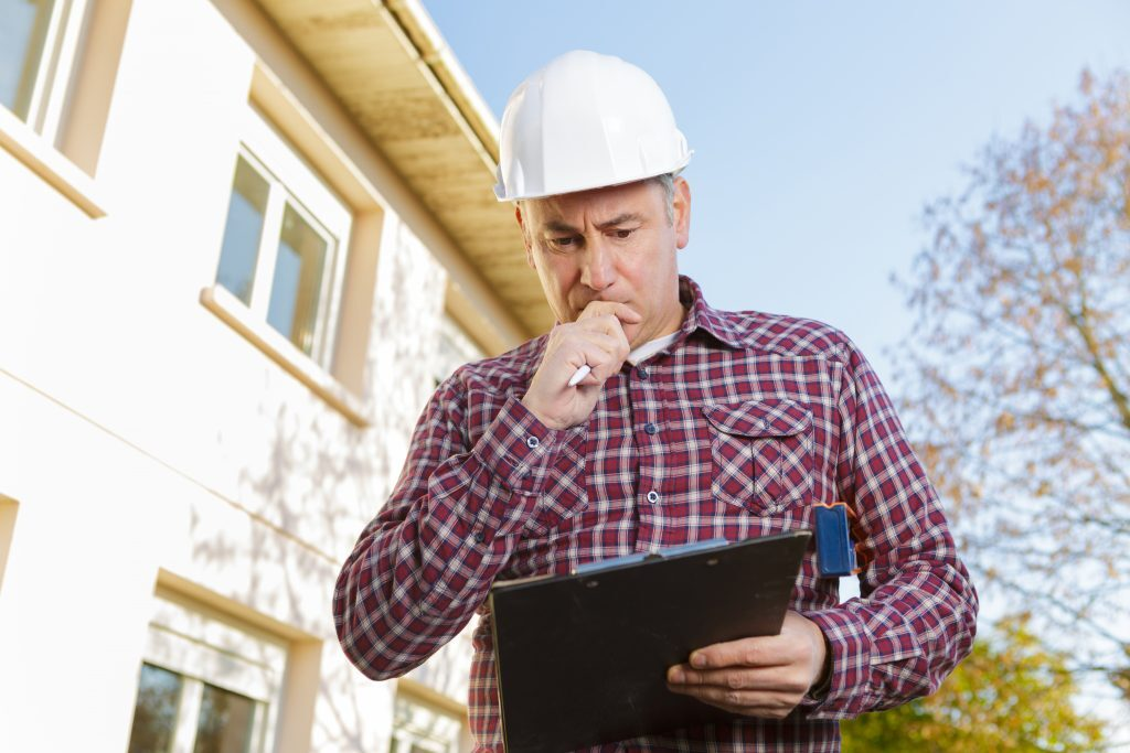 Insured roofer looking at a computer tablet
