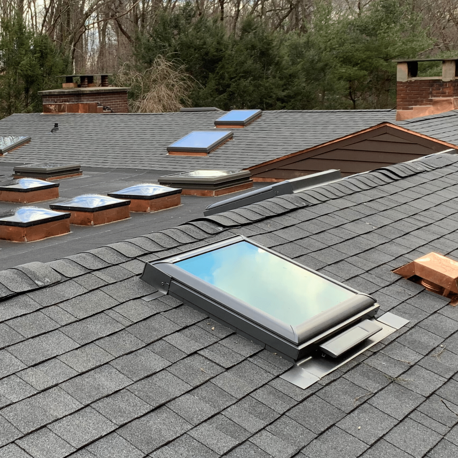 New asphalt roof installation with skylights and roof windows