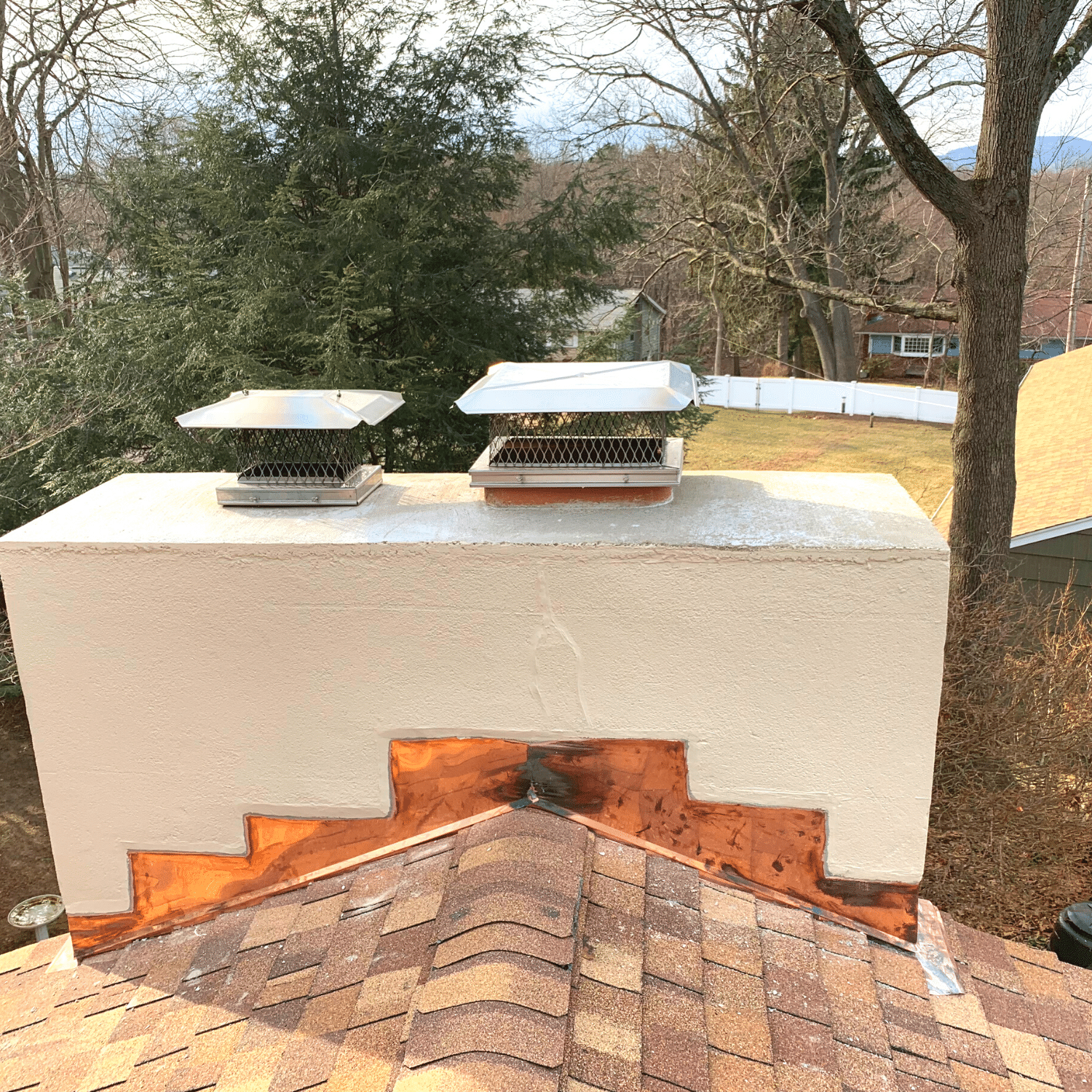 Masonry chimney with copper flashing with a tan asphalt roof in Westchester County, NY