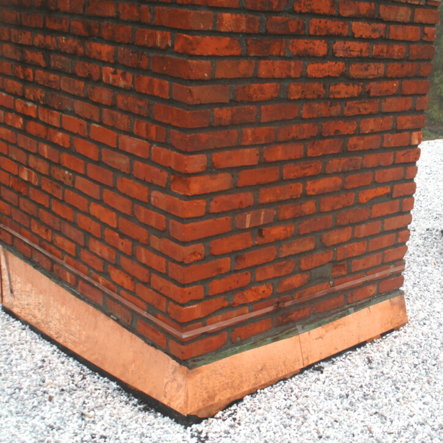 Brick chimney with copper flashing on residential asphalt roof in Hudson Valley